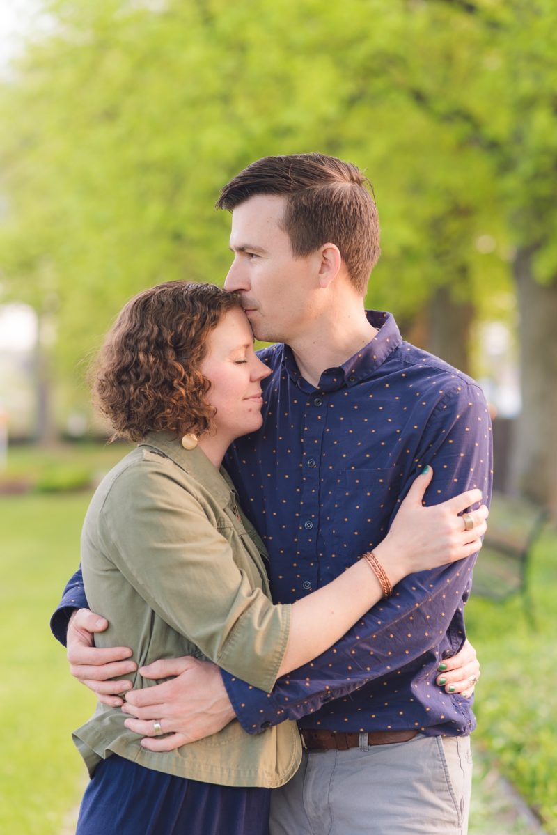 Husband and wife embrace in outdoor engagement photos